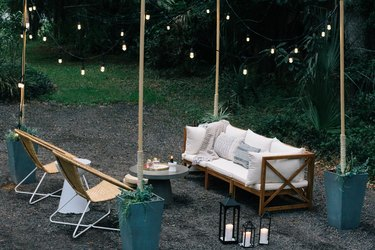 Patio furniture surrounded by string lights supported by wood poles