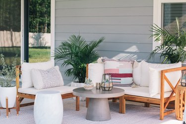 Round gray table with succulent terrariums and white cushioned deck furniture