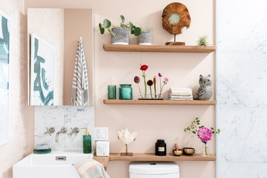 Bathroom with pink walls and wood shelving with flowers and plants