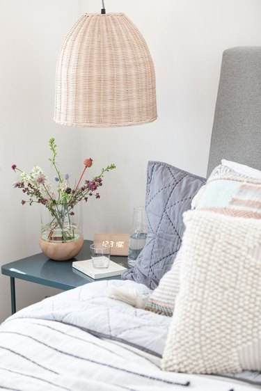 A wicker pendant lamp over a blue nightstand with flowers and bed with pillows