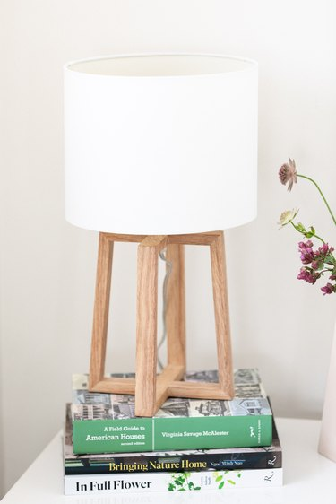 A lamp with a white shade and a wood base on top of books on a nightstand