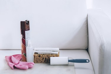 cleaning supplies including a lint roller, sponge, spray bottle, cloth, and furniture polish