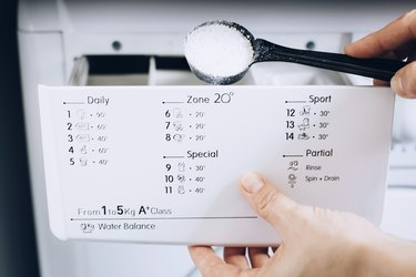 Hand using black measuring ladle to pour powder soap into second compartment of detergent compartment in white washing machine