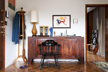 Wood credenza, sculptures, wood lamp, traditional art print, black spindle chair, coat rack, and wood checker floor.