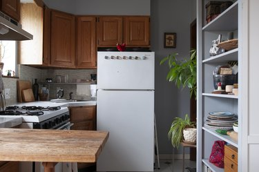 Kitchen with wood cabinets, white counters, gray tile backsplash, built-in shelve with dish ware, and plants.