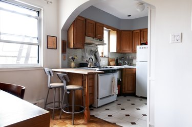 Wood cabinet kitchen with white counters, gray tile backsplash, and metal chair stools, brown-white tile floor.
