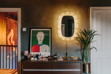 light up wall mirror and modern art on top of wood dresser