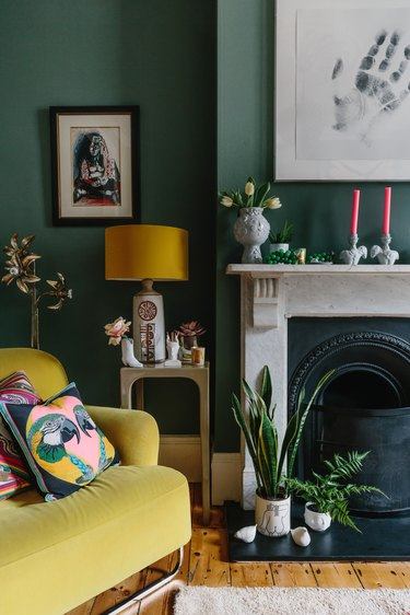 maximalist living room with green walls and vintage marble fireplace next to a yellow velvet armchair