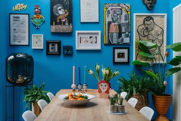 bright blue walls in a dining room with gallery wall art and white molded eames chairs at a wood dining table