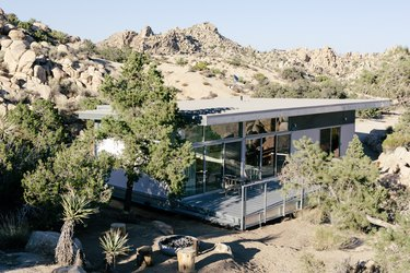 a pre-fab home with a glass and corrugated metal exterior and a large porch