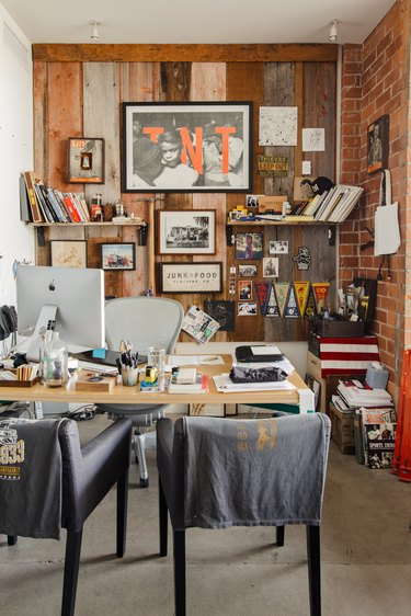 An office with varied wood panel and brick walls, eclectic art, shelves, wood desk, computer, and black chairs.