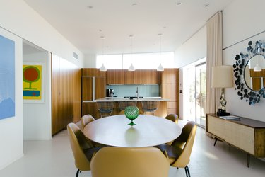 a dining area full of mid-century style, including mustard-yellow chairs, a low console, and a mirror with a starburst frame