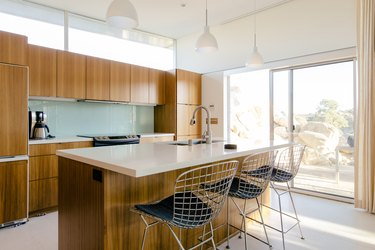 mid-century bar stools with metal mesh seats at a kitchen island