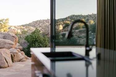 desert hills seen through large living room windows; a bar sink is in the foreground