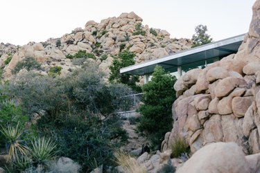 a corner of the house visible behind a wall of boulders