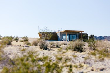 the exterior of a small desert house whose roof is curved like the hull of a ship