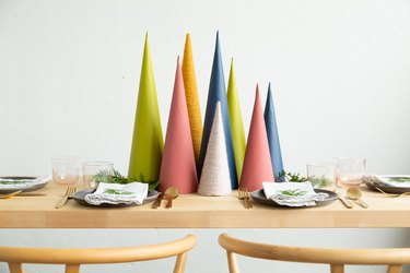 Christmas decor idea with a diy holiday centerpiece made of colorful cardboard cones, sprigs of greenery, and faux snow