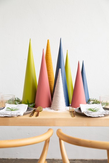 DIY Christmas decorations with a holiday centerpiece made of colorful cardboard cones, sprigs of greenery, and faux snow
