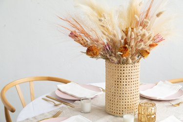 Vase wrapped in cane with dried flowers and grass on dining table