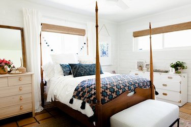 A wood bed post, with blue-neutral bedding, in a bedroom with wood furniture and blue-white decor.
