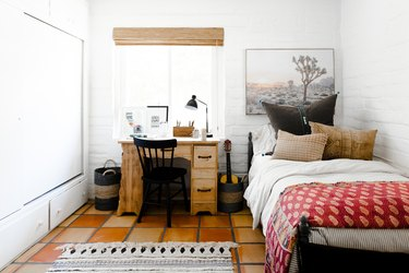 home office in kids bedroom with small wood desk in front of window