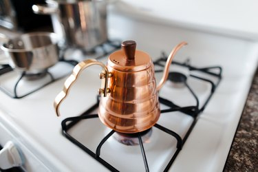 White gas stove with copper kettle