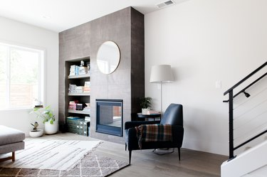 Living room with a gray accent wall, fireplace, round mirror, black armchair with a plaid blanket, layered rugs on a gray wood floor.