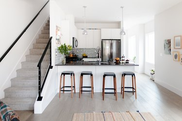 Wood stools at a gray counter kitchen island, with gray pendant lights. A kitchen with a gray backsplash. A gray carpeted staircase.