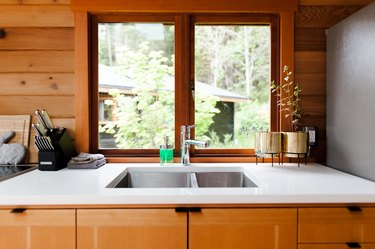 A white kitchen counter with a drop-in sink. Wood cabinets, walls, and window frame. Plants in gold planters.