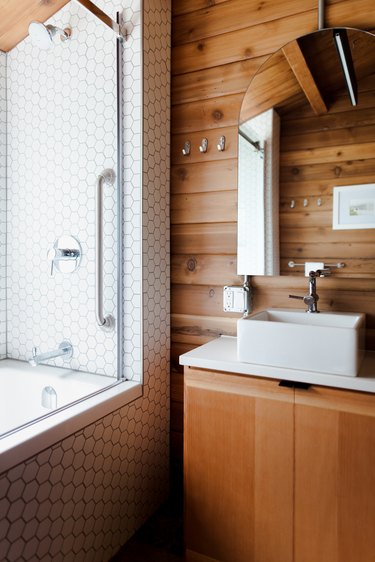 A bathroom with a wood vanity and wood walls. A square sink basin and an arched mirror. A shower with white hexagon tiles.