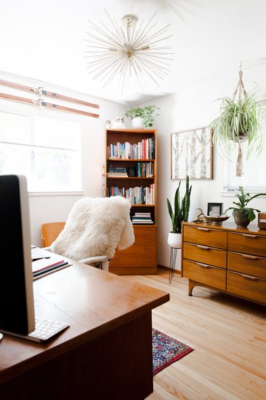 Home office with vintage wood furniture pieces and starburst chandelier