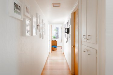 Wood floor hallway with built-in white cabinets, and framed wall photos.