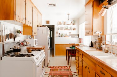 Wood cabinets in kitchen with traditional rug, wood dining furniture by white shelves with plants and pottery.