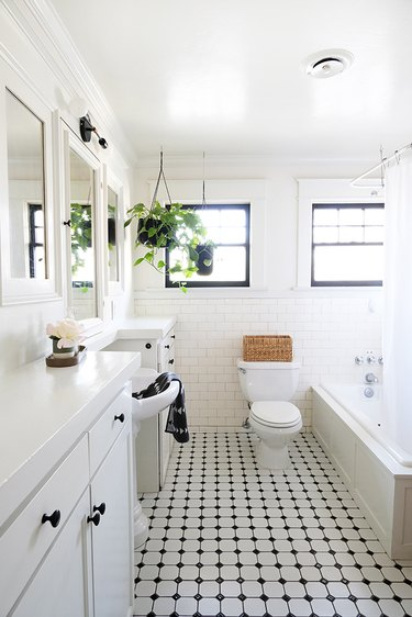 White walled bathroom with white-black tiled floor