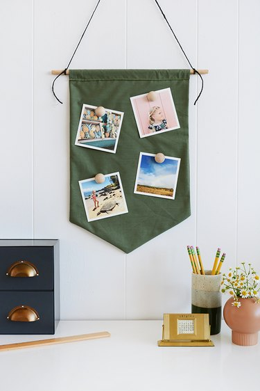 square photos attached to a green pendant with magnets attached to wooden knobs