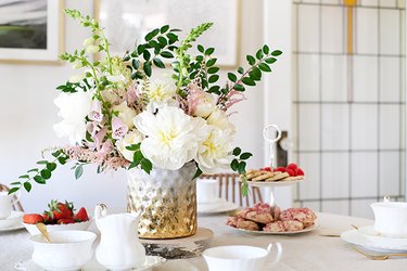 Textured gold-white vase with white and pink flowers on table with white china