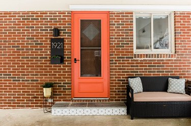 Brick house with an orange door, black wicker bench, gold plant stand, and black sconce light