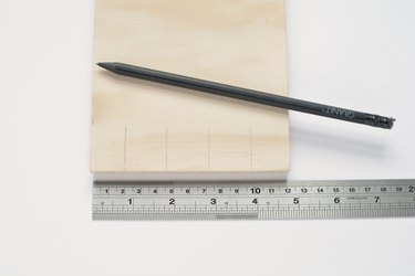 a ruler and a pencil next to a square of plywood that has pencil marks at regular intervals