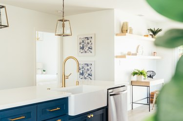 Dark blue kitchen island cabinets with gold hardware, white countertop, and gold sink faucet. Gold lantern pendant lights and wood shelves.