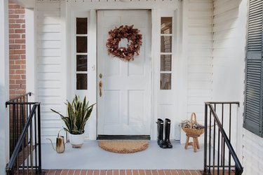 Concrete porch and brick front steps of a white house with a floral door wreath
