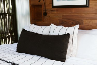 White and black bedding in wood paneled room