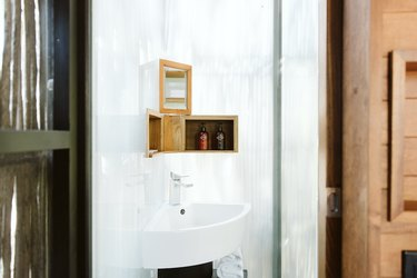 Small corner bathroom sink with small wooden shelves and bath products