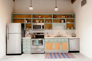 Kitchen with light blue-wood cabinets, art deco pendant lights, and an ornate wall grille vent, and purple-pink floor rug.