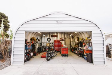White garage with motorcycle, storage cabinets, and shelving