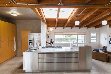 Industrial kitchen with a wood ceiling, skylights, globe pendant lights, wood cabinets, and a metal or steel kitchen island.