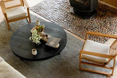 Two wood-cane accent chairs on a gray rug, with a round black coffee table. A stove fireplace and a stone hearth.