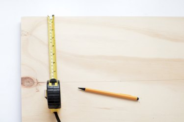 using a tape measure and pencil to mark where moulding will go on a plywood sheet