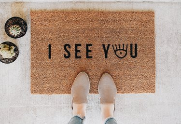 """a woman's shoes on a brown doormat with black letters spelling """"out i see you""""--the """"o"""" in """"you"""" is an eye graphic"""