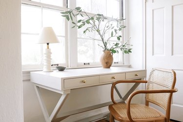 white desk with geometric white lamp and vintage wood chair