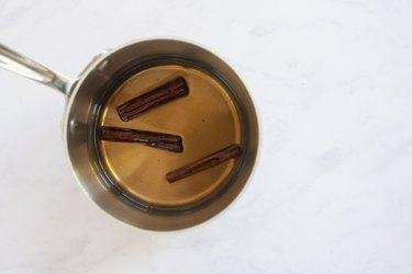 cinnamon sticks in liquid in pan
